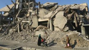 """Zerstörte Erinnerungen in Rakka: Eine Frau schiebt einen Kinderwagen durch die zerstörte Stadtlandschaft von Rakka in 2019. Fotograf Abood Hamam sagt: """"2017 begann ich, meine Heimatstadt zu fotografieren. Mit jeder Ecke hier verbinden mich Erinnerungen. Sie haben all das zerstört. Meine Bilder werden mal historische Dokumente sein."""""""