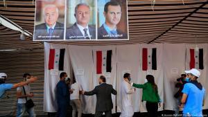 Wahllokal für syrische Bürger im Libanon in einem Zelt. Die Wahlkabinen sind mit Tüchern abgeteilt, an denen syrische Flaggen befestigt sind. Von der Decke hängen die Porträts der drei Kandidaten. Ordner weisen den Wählern freie Wahlkabinen zu; Foto: Hussein Malla/AP-Photo/picture alliance