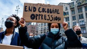 16 May 2021, Amsterdam, Niederlande, eine schwarze Frau hält bei einer Demonstration  ein Plakat gegen Kolonialismus hoch. In Amsterdam haben sich Tausende am Dam Platz versammelt, um israelische Angriffe und Zwangsenteignungen von Palästinensern in Sheikh Jarrah im besetzten Ost-Jerusalem zu verurteilen: Foto: Ana Fernandez/Zumo Wire/imago images