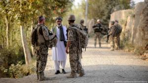 Ein Bundeswehrsoldat (l) und ein Dolmetscher (r) sprechen nahe Kundus im Distrikt von Char Darreh mit einem Mann (photo: dpa-Bildfunk)