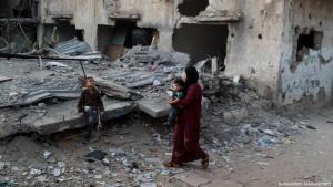 Eine palästinensische Frau und zwei Kinder schauen nach den Überresten ihres Hauses in Gaza, das bei einem israelischen Luftangriff im Juni 2021 zerstört wurde; Foto: Mohammed Salem/Reuters