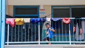 Ein Junge auf einem Balkon schaut durch das Geländer, auf dem Wäsche zu Trocknen aufgehängt ist; Mahmoud Khattab/Zumapress/picture-alliance