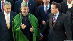 """Petersberg bei Bonn, der UN-Sondergesandte für Afghanistan Lakhdar Brahimi, der afghanische  Präsident Hamid Karzai und der damalige Bundeskanzler Gerhard Schröder (von links nach rechts) stehen für ein """"Familinefoto"""" zusammen am 2. Dezember 2002 zum Beginn der internationalen Afghanistankonferenz (Foto: picture-alliance/dpa)"""