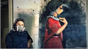 Shamsia Hassani sitzt mit einer Atemschutzmaske vor einem ihrer Werke, dass eine Frau im roten Kleid zeigt; Foto: Shamsia Hassani