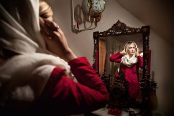 Ein Tuch über die blonden Haare, ein Mantel über die westliche Kleidung: Eine Iranerin bereitet sich darauf vor, ihr Haus zu verlassen. Das Schönheitsideal im Iran sei ein Spagat zwischen Tradition und Moderne, erklärt die Fotografin Samaneh Khosravi. Viele Iranerinnen eifern dem Aussehen von Hollywood-Schauspielerinnen nach, die sie über das Internet oder das Satellitenfernsehen verfolgen.