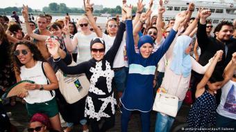 """Es ist kein richtiger Strand und auch nicht Frankreich - trotzdem setzten rund 100 Belgierinnen und Belgier ein Zeichen gegen das - mittlerweile gerichtlich wieder gekippte - Burkini-Verbot an Frankreichs Stränden. """"Jede Frau und jeder Mann sollte selbst entscheiden, was er tragen möchte"""", sagte eine in Bikini gekleidete Frau auf der Veranstaltung."""
