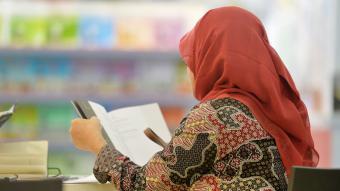Muslima mit Kopftuch liest aus einem Buch; Foto: picture-alliance/F. May