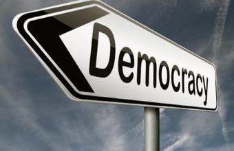 """Schild mit der Aufschrift """"Democracy""""; Quelle: azfemina.com"""