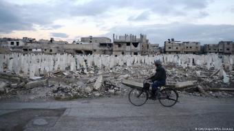 Mann passiert Straße mit Gräbern am Rande der syrischen Stadt Douma; Foto: Getty Images/AFP