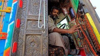 Ein Fahrer öffnet die Tür zu der aus Holz geschnitzten Fahrerkabine seines dekorierten LKWs.
