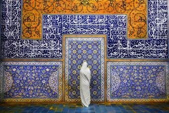 Eine Frau steht in der Sheikh Lotfallah-Moschee in Isfahan, Iran. Diese Moschee ist ein wahres Meisterwerk iranischer Architektur und Raffinesse. Diese Moschee wurde zwischen 1602 und 1619 in der Safawiden-Zeit gebaut. Die dekorativen Ornamente sind atemberaubend anzusehen.