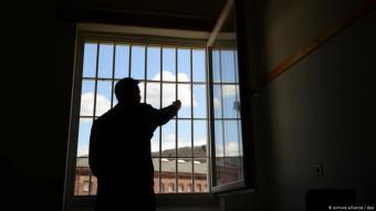 Häftling in einer Gefängniszelle von hinten am Fenster stehend.